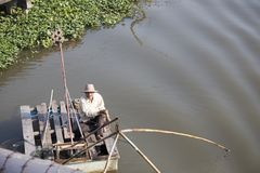 Old fisherman floating on river and fishing with net Stock Photos