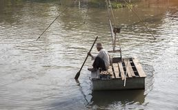 Old fisherman floating on river and fishing with net. 6 Febuary 2018,Bangkok,THailand. Old fisherman floating on river and fishing with net and wood boat in the Stock Photo