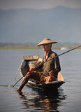 An old  fisherman on inle lake,myanmar. An old fisherman using his leg to hold down a fishing trap on inle lake in myanmar (burma Stock Images