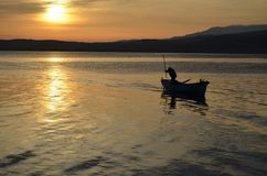 An old fisherman on the lake at sunrise stock images