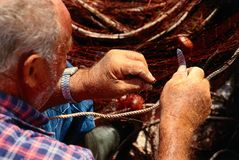 Old fisherman mending net Stock Images