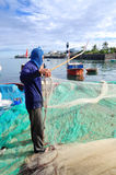 An old fisherman is removing anchovies fish from his fishing net to begin a new working day in Ly Son island Stock Photos
