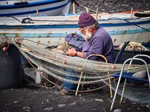 Old fisherman repairing his fishing nets on Stromboli island, Sicily, Italy stock photo