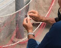 Fisherman is fixing a fishing net. Old fisherman reparing fishing net, sitting with pipe in his mouth royalty free stock image