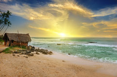 Old fisherman`s hut on shore of picturesque ocean and beautiful Stock Photography