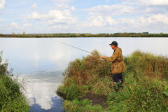Old fisherman with spinning rod Royalty Free Stock Photo