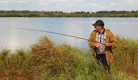 Old fisherman with spinning rod Stock Images