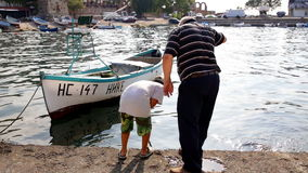 The old fisherman is teaching the boy to catch a net of clams stock video footage