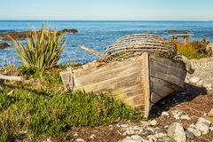 Old fishermans boat with a lobster trap on a beach Royalty Free Stock Photos