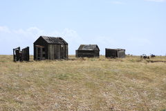 Old fishermans huts in Dungeness. A small group of old fishermans huts under a pale blue sky at Dungeness Stock Images