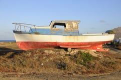 Old fishermen boat abandoned on shore stock images