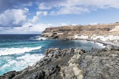 Old fishermen`s village Los Molinos with cliffs and rocks with blue churning ocean and sky Stock Image