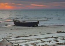 Old fishing boat anchored at sandy beach Royalty Free Stock Image