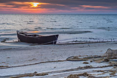 The old fishing boat on the beach of Baltic sea at sunrise Royalty Free Stock Photography