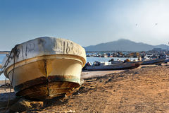 Old fishing boat on the beach in the port of Kalba Stock Photos