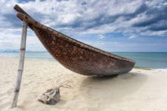 Old fishing boat. On the beach surounded by white shore and great blue sky. Vietnam. Phu Quoc island Stock Photo