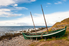 Old fishing boat, boat of the Vikings on the ocean shore, Iceland Royalty Free Stock Images