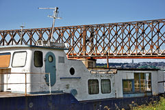 Old fishing boat and bridge behind Stock Image