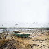 Old fishing boat at coast. Foggy in the morning Stock Image