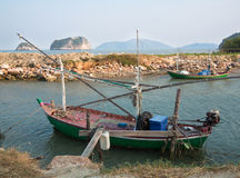 Old fishing boat is docked on the background of the shore rocks Stock Photography