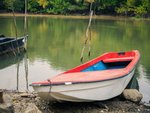 An old fishing boat fastened to a wooden sticks on the river shore. Stock Photo