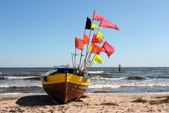 Old fishing boat with flags. On shore line Stock Image