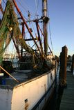 Old Fishing Boat Galveston. Old rusting fishing boat tied up at dock at sunset at the port in Galveston Texas showing fishing nets floats and tackle Stock Photo