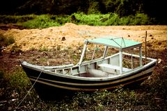 Old fishing boat that have been abandoned at Malaysian beach stock photo