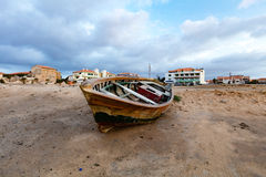 Old fishing boat on land. Old wooden fishing boat on sandy land in a town. Early morning Royalty Free Stock Image