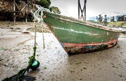 Old fishing boat is moored on beach at low tide. Royalty Free Stock Photos