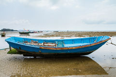 An old fishing boat moored beached on the beach at low tide. Stock Images