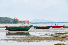 An old fishing boat moored beached on the beach at low tide. Stock Image