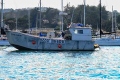 Old fishing boat moored in a harbor. With yachts and motorboats viewed side on in calm water stock photos
