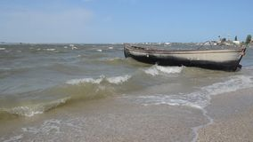 An old fishing boat moored to the shore. Swaying on the waves. On the cobbled shore of the Black Sea estuary stock video footage