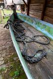 An old fishing boat with a mooring rope at the bottom. A thick rope at the bottom of the boat. Place - open-air museum, background, beach, blue, closeup, deck stock photos