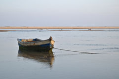 Old fishing boat resting on the low tide Stock Images