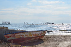 Old fishing boat and ruined oil rig Royalty Free Stock Photo