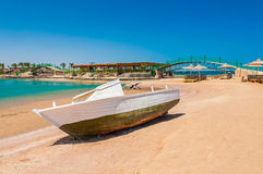 Old fishing boat on sand with blue sky and water Stock Image