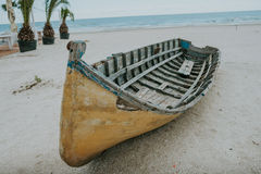 Old fishing boat on sand with blue sky and water Royalty Free Stock Photos