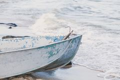 Old fishing boat on the seashore. Is washed by the sea wave Royalty Free Stock Image