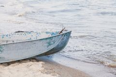 Old fishing boat on the seashore. Is washed by the sea wave Stock Photography