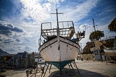 Old fishing boat on the shore. A ship pulled ashore. Harbor in the village of Hersonissos on the island of Crete, Greece. stock images