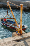 Old fishing boat and small crane in port Stock Image