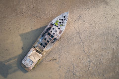 Old fishing boat standing in the mud sea. Aerial view from flyin Stock Photos