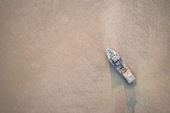 Old fishing boat standing in the mud sea. Aerial view from flyin Royalty Free Stock Images