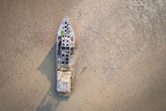 Old fishing boat standing in the mud sea. Aerial view from flyin Royalty Free Stock Photography