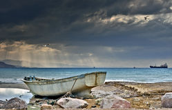 Old fishing boat on a stony beach Stock Photo