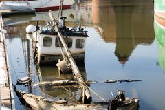 An old fishing boat. An old sunken fishing boat in the port. Season of the early spring Royalty Free Stock Photo