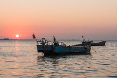 Old fishing boat at sunset time Stock Photos