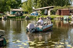Old fishing boat and swampy banks of the Dnieper River. River fishing in Eastern Europe Stock Photos